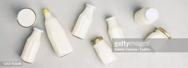 directly above shot of milk bottles over white background - milk bottle stock pictures, royalty-free photos & images