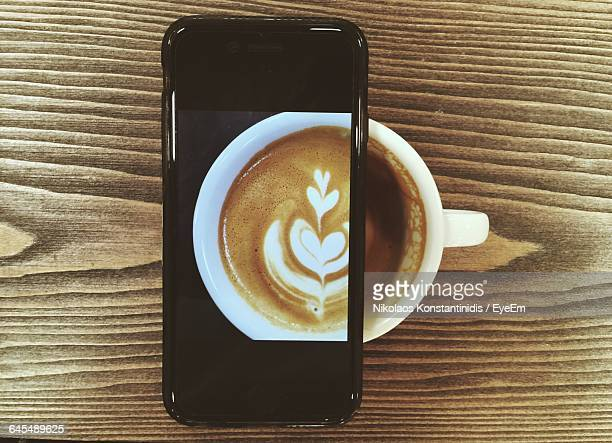 Directly Above Shot Of Mobile Phone On Coffee Cup At Cafe