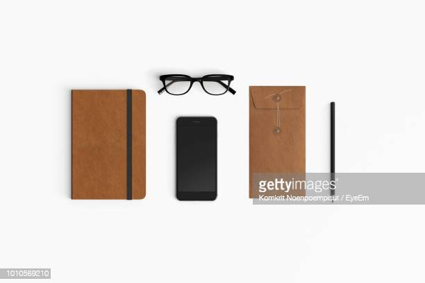 directly above shot of mobile phone with book and eyeglasses over white background - office supply stock pictures, royalty-free photos & images