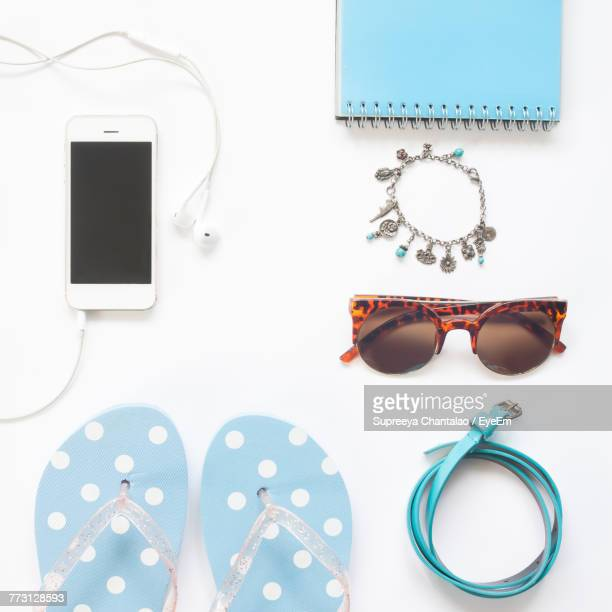 Directly Above Shot Of Mobile Phone With Book And Slippers Over White Background