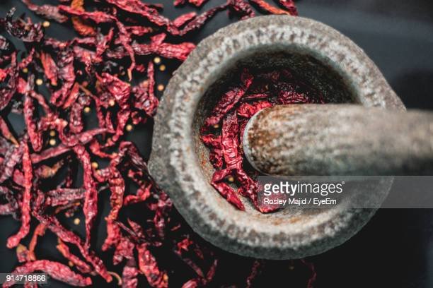 Directly Above Shot Of Mortar And Pestle By Dry Red Chili Peppers