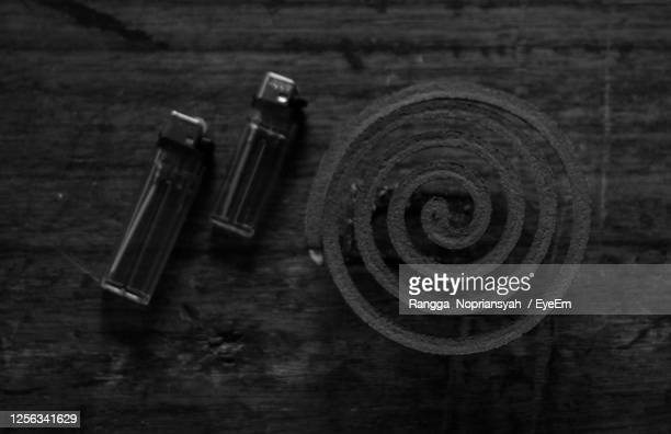 directly above shot of mosquito repellent coil with cigarette lighter on table - incense coils stock pictures, royalty-free photos & images