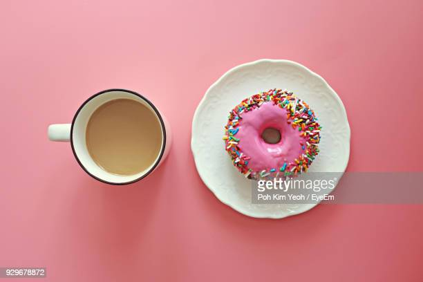 directly above shot of multi colored donut and coffee on pink background - donut stock pictures, royalty-free photos & images