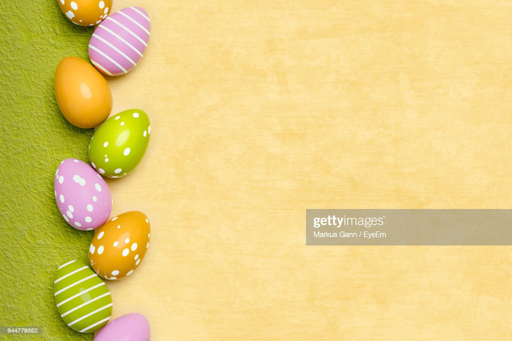 Directly Above Shot Of Multi Colored Easter Eggs On Yellow Table : Stock Photo