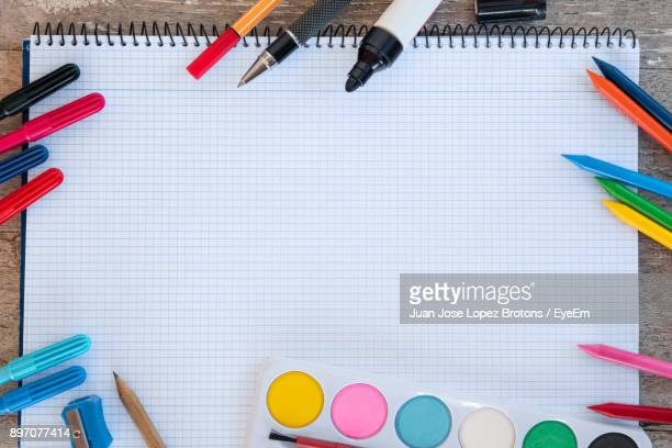 directly above shot of multi colored pencils and spiral notebook on table - art and craft equipment stock pictures, royalty-free photos & images
