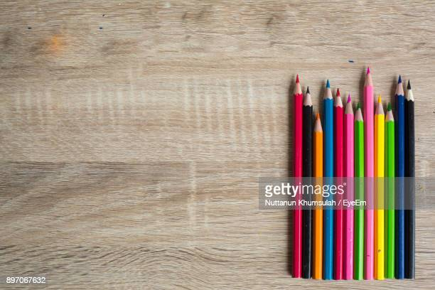 directly above shot of multi colored pencils on wooden table - color pencil stock pictures, royalty-free photos & images