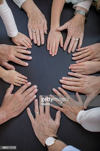 Directly above shot of multi-generation family placing hands in circle