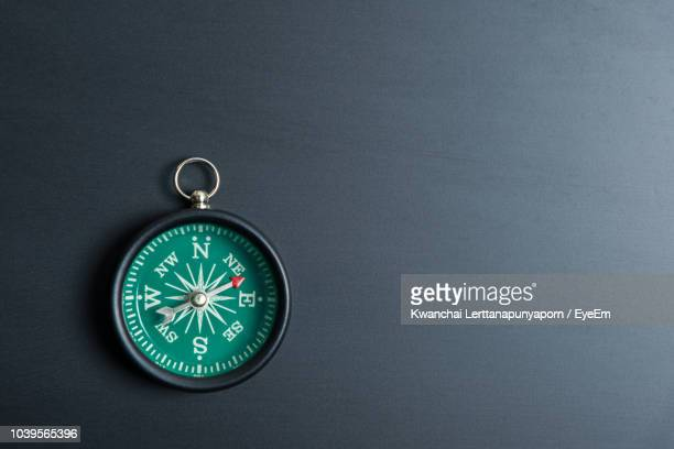 directly above shot of navigational compass on table - compass stock pictures, royalty-free photos & images