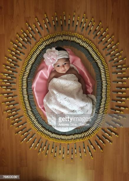 directly above shot of newborn lying on hardwood floor amidst syringes - one baby girl only stock pictures, royalty-free photos & images