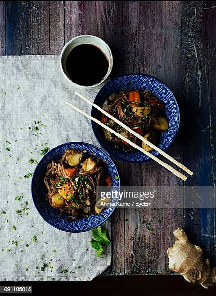Directly Above Shot Of Noodles In Bowl With Chopsticks On Wooden Table