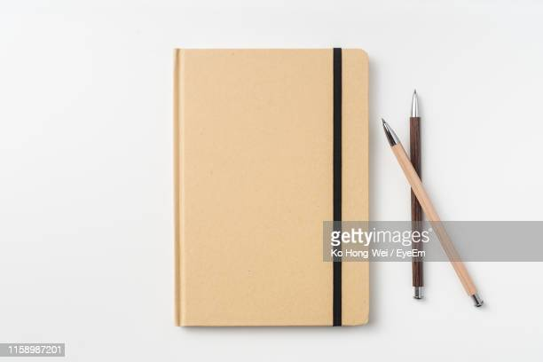 directly above shot of note pad and pens on white background - kugelschreiber stock-fotos und bilder