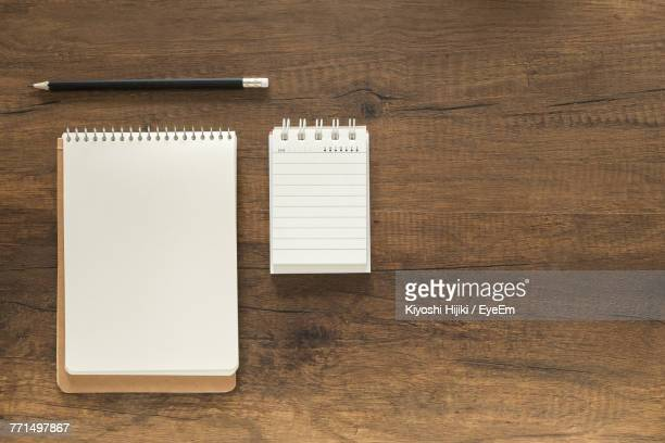 directly above shot of note pads and pencil on table - lined paper stock photos and pictures