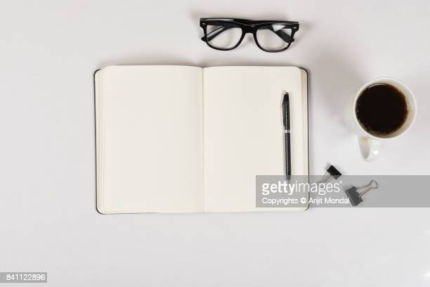 Directly above shot of notebook page, pen, spectacle, coffee cup on white office desk