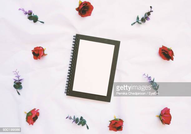 Directly Above Shot Of Notebook With Flowers On White Background