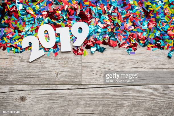 directly above shot of number 2019 and confetti on wooden table - 2019 stock pictures, royalty-free photos & images