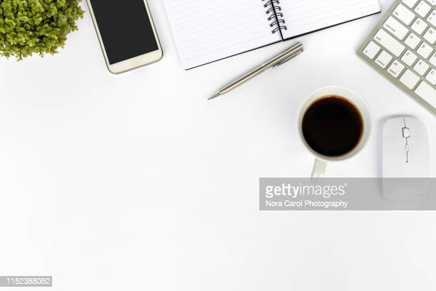 directly above shot of office desk and stationery on white background - bureau stockfoto's en -beelden