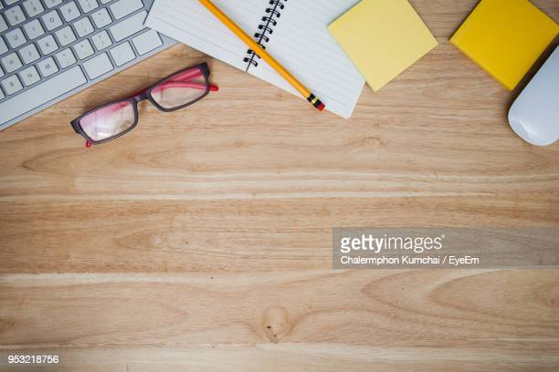 directly above shot of office supplies on wooden table - 机 ストックフォトと画像