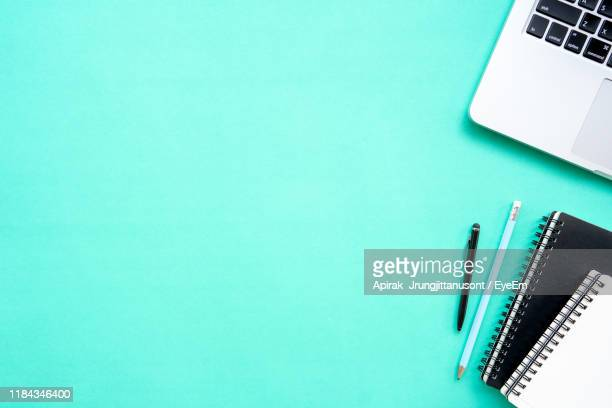 directly above shot of office supplies over turquoise background - ターコイズカラーの背景 ストックフォトと画像