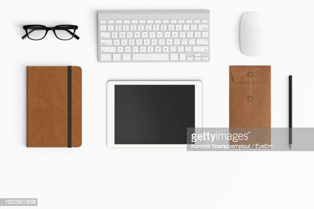 directly above shot of office supplies over white background - computertoetsenbord stockfoto's en -beelden