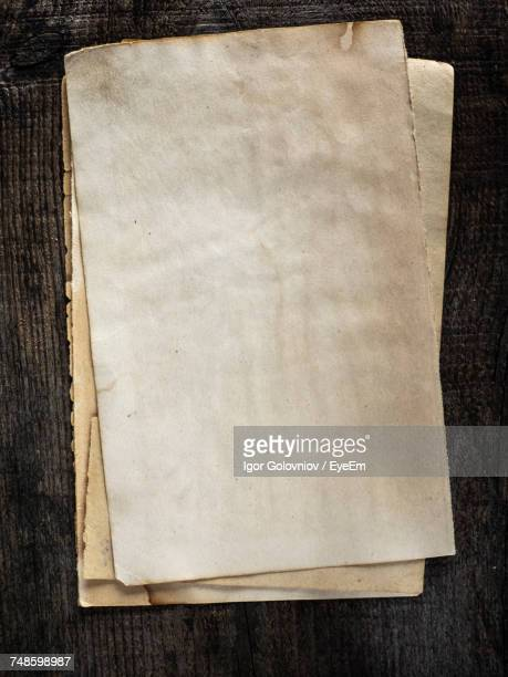 directly above shot of old blank pages on wooden table - igor golovniov stock pictures, royalty-free photos & images