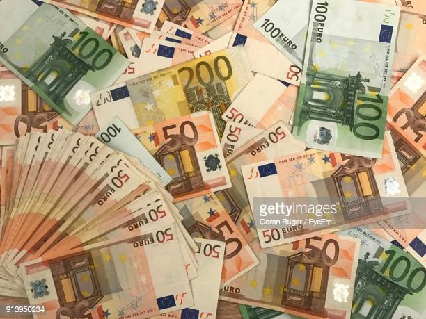 directly above shot of on paper currency at table - banconote euro foto e immagini stock
