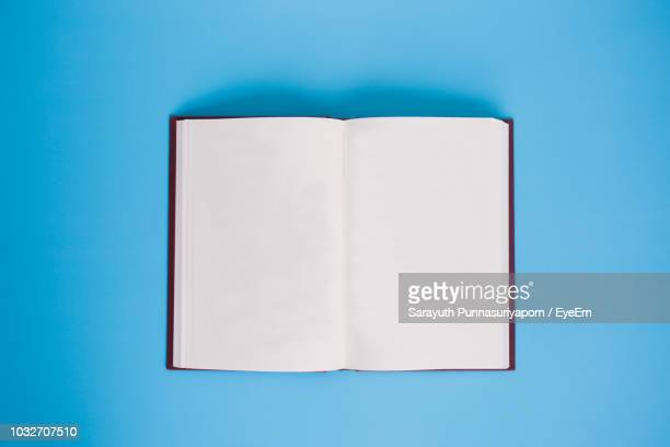 directly above shot of open book against blue background - book stock pictures, royalty-free photos & images