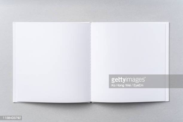 directly above shot of open book on gray background - unbeschrieben stock-fotos und bilder