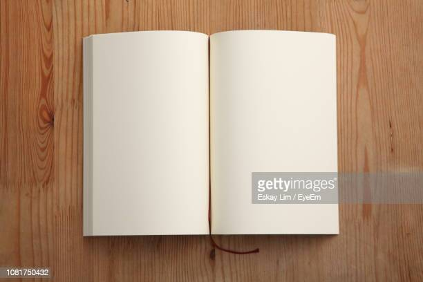 directly above shot of open book on table - book stock pictures, royalty-free photos & images