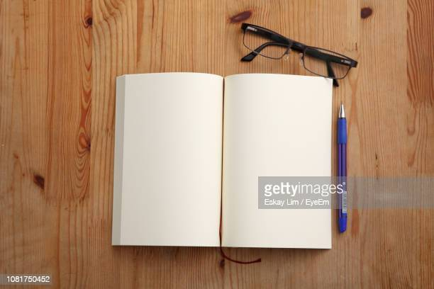 directly above shot of open book on table - textbook stock pictures, royalty-free photos & images