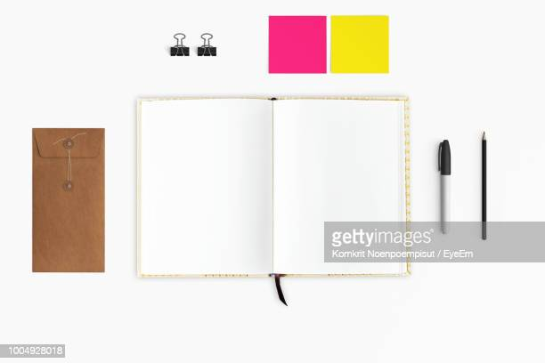 Directly Above Shot Of Open Book With Adhesive Notes And Envelope Over White Background