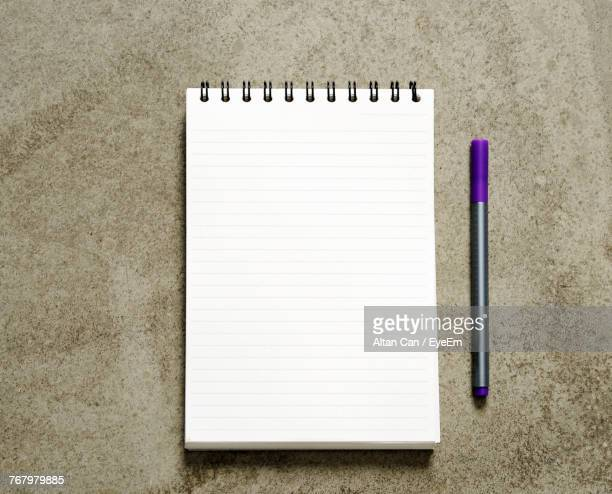 directly above shot of open book with pen on table - lined paper stock photos and pictures