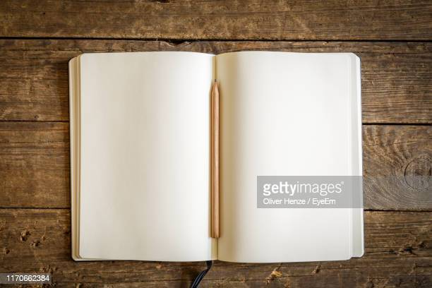 directly above shot of open book with pencil on table - carnet photos et images de collection
