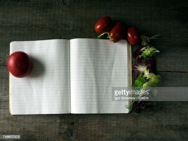 directly above shot of open cookbook with tomatoes and herbs on table - kochbuch stock-fotos und bilder