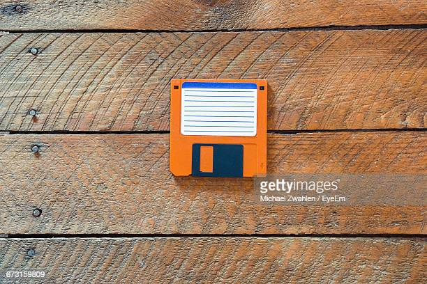 Directly Above Shot Of Orange Floppy Disk On Wooden Table