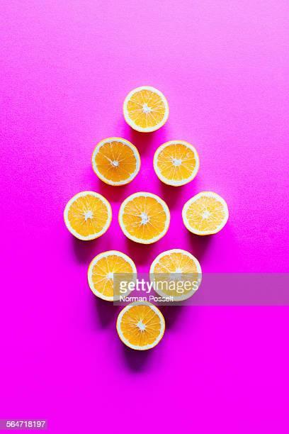 Directly above shot of orange slices arranged in diamond shape on pink background