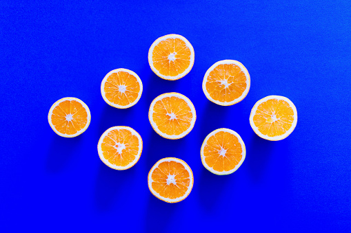 Directly above shot of orange slices arranged in diamond shape on blue background - gettyimageskorea