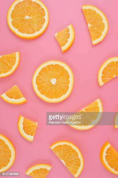 directly above shot of orange slices on pink background - orange farbe stock-fotos und bilder