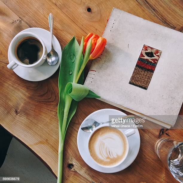 Directly Above Shot Of Orange Tulips Amidst Coffee And Menu On Table