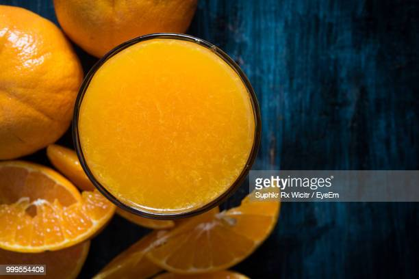 directly above shot of oranges by juice in glass on table - orange juice stock pictures, royalty-free photos & images