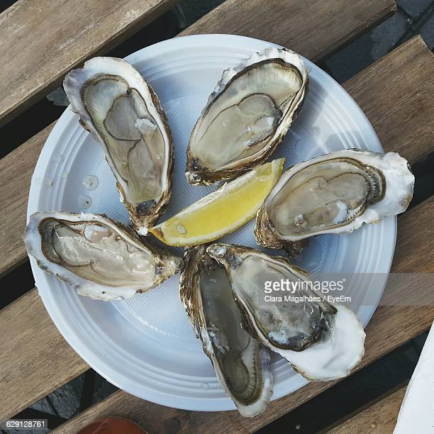 Directly Above Shot Of Oyster Shells Served With Lemon In Plate On Wooden Table