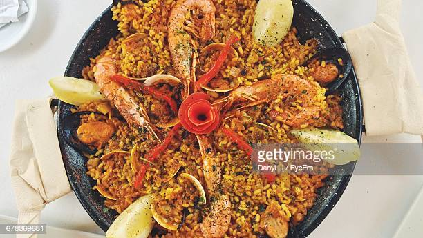 directly above shot of paella in cooking pan on table - paella stock photos and pictures
