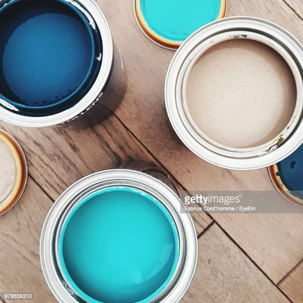 directly above shot of paint cans on table - farbdose stock-fotos und bilder
