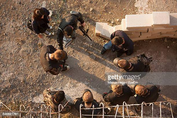 Directly Above Shot Of Paintball Players Preparing And Planning Game On Field