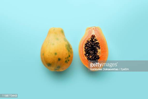 directly above shot of papayas on blue background - tropical fruit stock pictures, royalty-free photos & images