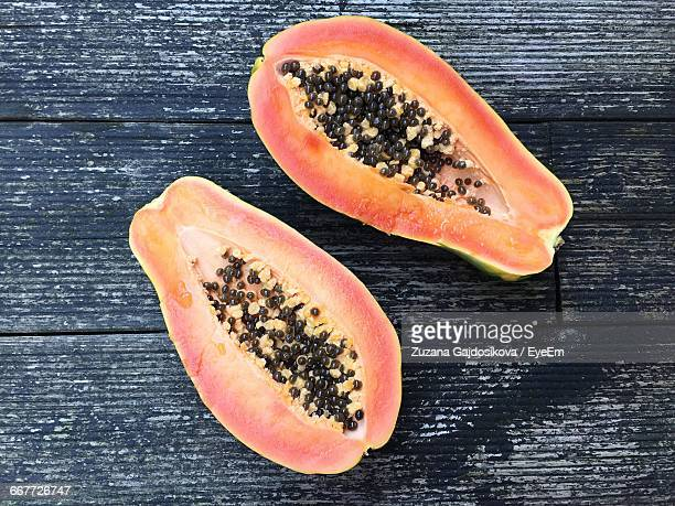 directly above shot of papayas on wooden table - papaya stock photos and pictures