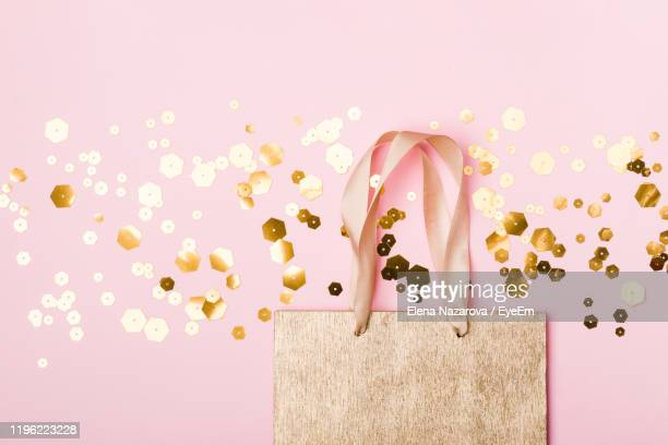 directly above shot of paper bag with confetti on pink background - 取っ手 ストックフォトと画像