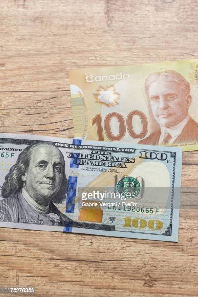 directly above shot of paper currency on wooden table - canadian one hundred dollar bill stock pictures, royalty-free photos & images