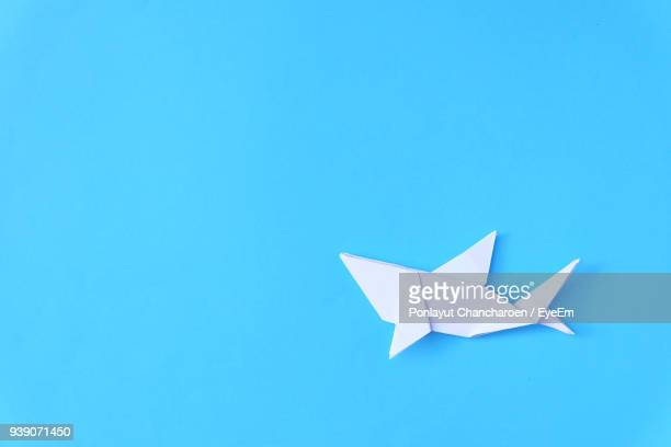 directly above shot of paper fish over blue background - origami photos et images de collection