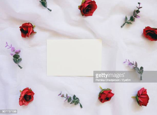 Directly Above Shot Of Paper With Artificial Flowers On Fabric