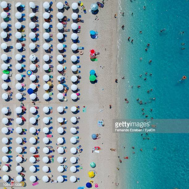 directly above shot of parasols and people at beach during sunny day - large group of objects stock pictures, royalty-free photos & images